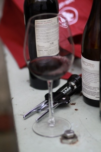 Glass of wine with bottles and opener